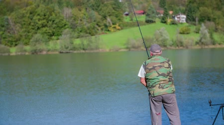 fishermen : A man fishes in the lake. Slow motion RAW footage of a man standing close to the lake and fishing in it in the middle of a countryside on a sunny day.