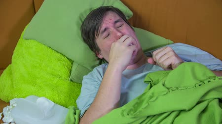 viski : Hard sneezing by ill man . Sick man laying at home and sneezing and clinging his nose with a tissue,footage is taken close up slow motion.