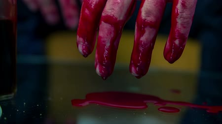 bandagem : Blood dripping from hands . Man home alone beaten and with hands hanging  over the glass table and the blood is dripping on it ,footage taken in slow motion.