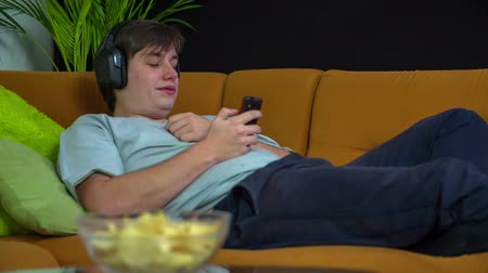 brambory : Moving head to the bit . Young man relaxing on a sofa in living room with headphones and moving to the bit in slow motion.