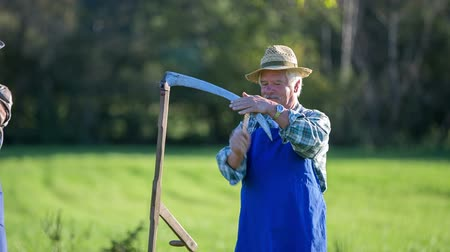 один человек : Elderly farmer sharpen the scythe on traditional way. Close up footage of a elderly man sharpening the scythe on traditional way with a grinder on the countryside on the sunny day.