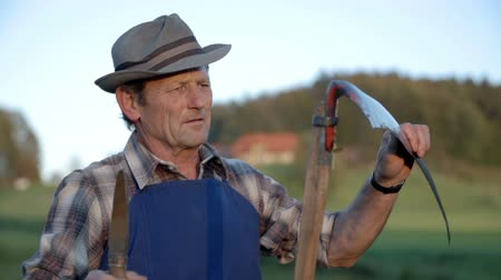 çiftçi : Middle age farmer clinging the scythes blade with grass. Slow motion close up RAW footage of a middle age farmer clinging the blade of scythe with grass and the sun is shining in his face in the countryside.