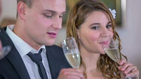 медовый месяц : A sip of good champagne after the formal part of wadding . Close up RAW footage of a just married couple taking  a sip of champagne after the formal part of wadding in the mayors office.