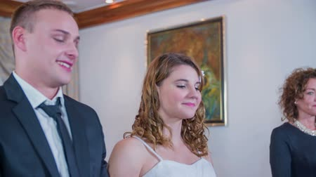 evli : SENTJUR SLOVENIA  OCTOBER 2014: Two young people getting married  . Slow motion RAW footage of a Registrar walking to the table and the people at the wadding sending up to start it . Stok Video
