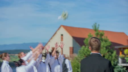 bouquets : SENTJUR SLOVENIA  OCTOBER 2014: Total RAW footage of a couple after the wedding and the bride throws the bouquet on a sunny day on a countryside.