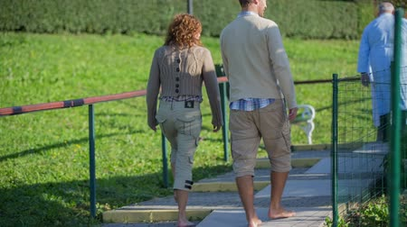 traverse : Couple walk barefoot on the footpath in the park. Zooming-out RAW footage of a middle age couple walks barefoot on the path in the beautiful park in a countryside.