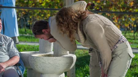 traverse : Couple comes to drink some water . Slow motion RAW footage of a couple stops so man can drink some water in the park on a sunny day.