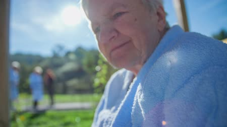 traverse : Elderly woman with greenery in her hands . Slow motion close up RAW footage of a woman seating in the park with greenery in her hands on a sunny day.