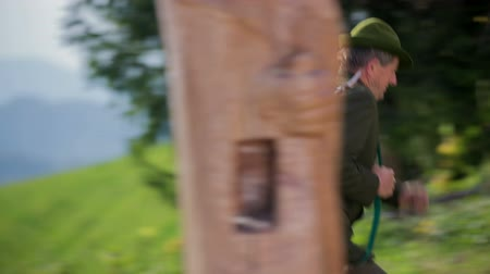 sniper scope : Hunter starts running up hill. Close up RAW footage of a elderly hunter start running up the hill in the forests on a sunny day in the countryside. Stock Footage