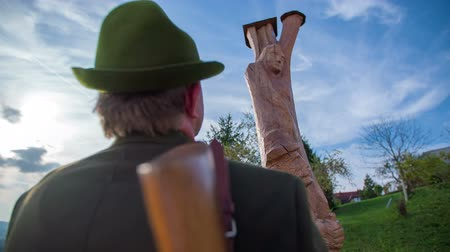 sniper scope : Hunter looking at the top of the statue. Slow motion close up RAW footage of a hunter looking in the top of the statue on a sunny day in the countryside. Stock Footage