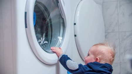 kondenzátor : Interesting motion of a washer. Young boy standing next to the washer and looking the clothes washing in a washer, slow motion footage.