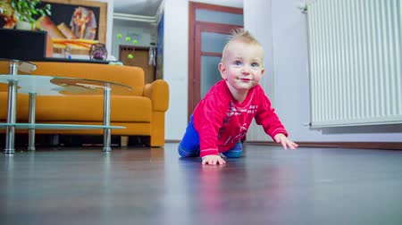 белый : Young cut boy in red shirt crawling in the middle of a living room towards his father, footage in slow motion.