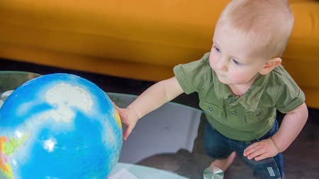 global : Young cute boy standing at the glass table in the living room looking at a globe, footage taken in slow motion.