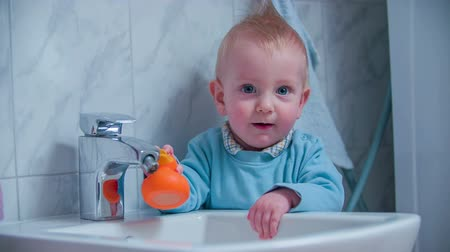 wanna : Young boy standing in the bathroom with a duck in his hands looking in the camera, footage in slow motion.