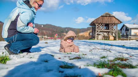 deslizamento : Cute young boy firs time on snow with his mother on a filed on a sunny day in a countryside, footage in slow motion. Vídeos