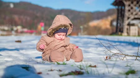 deslizamento : Young cut boy seating on a filed full of snow and the mother is playing with him on a sunny day in countryside.