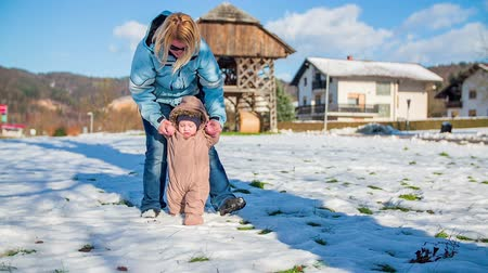 deslizamento : Young boy with her mother walking outdoors on a snow and learn how to walk, footage is in slow motion.