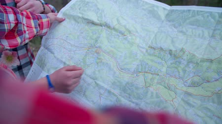 церковь : Children looking in to the map and looking where they are in the middle of a countryside, footage is taken in slow motion. Стоковые видеозаписи