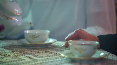 old times : Lady is picking up the tea pot and pouring some tea in to the cup at the vintage table, historic close up footage.