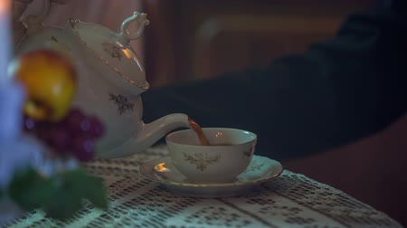 old times : Close up footage when the tea is poured in to the cup on the wooden table in the vintage room.