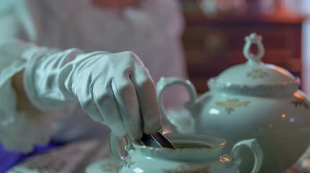 sentiment : Lady opens the lid of a sugar and picking up one cube and giving it to the man in to the tea, close up footage in slow motion.