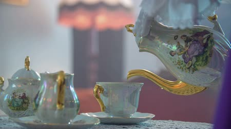 old times : Lady is starting pouring a hot tea in to the cap on the wooden table, close up footage taken in slow motion.