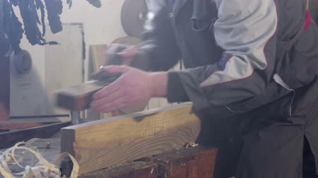 bandsaw : Worker working with wood and smoothing the edge of a wooden plank on a bench table, footage in slow motion.