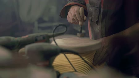 munkaeszközként : Wood master making a print with hot steel on a wooden board on a working bench, footage in slow motion.