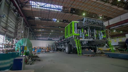 montagem : Mining machinery standing in the middle of a hall and getting build, total footage taken in sow motion.