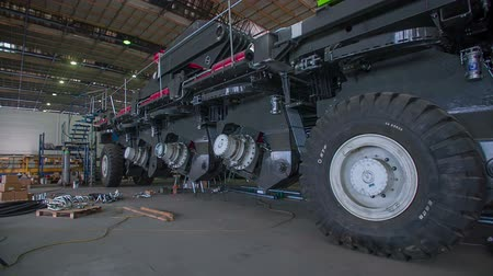 montaj : Mining machine getting build in big factory and standing on a big tires, footage is in slow motion. Stok Video