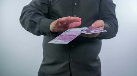 финансы : Man with a pile of bills in his hands and he starts to throw them away, slow motion footage.