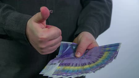 throwing in : Man standing with a big pile of money in his hands and hi spreads it out, footage is taken in slow motion.