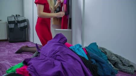 dressing room : In the middle of the bed room is a pile of clothes made  by a young woman cleaning the closet, footage in slow motion. Stock Footage