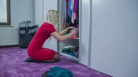 dressing room : Old clothes are thrown on the bedroom flour out of a closet so young woman can put in a new clothes.