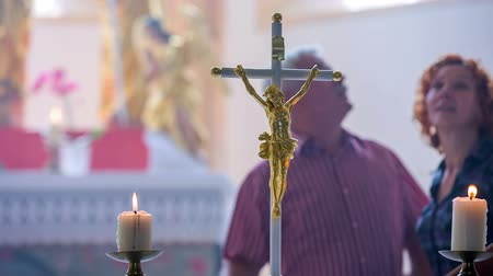 clergy : An older Christian couple is walking around the altar holding each others hands. There are two burning candles on the altar. Statues are in the background. Stock Footage
