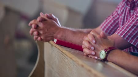 clergy : Two older Christians are praying in church. The man opens the Bible and reads it. Close-up shot fast motion Stock Footage