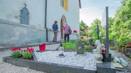 clergy : Two older people are walking up to the church entrance. The man leaves his pilgrims staff on the churchs entrance. The cemetery is in front of the church Stock Footage