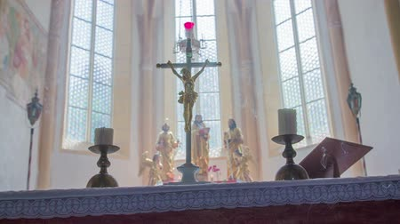 clergy : Close-up shot with the candles and cross on the altar. In the background, there are windows  and church statues.