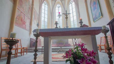 clergy : The church altar in the front. Two blowing candles on the side. There is a cross on the altar. In the background, there are windows and statues. Beautiful interior design with carpets and chairs and flowers