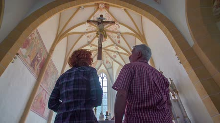 clergy : Couple walking in church and looking up. Cross hanging down the ceiling. The altar, paintings and windows in the background. Close-up shot