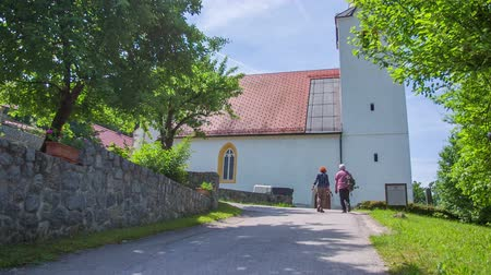 clergy : An older couple is walking up to the church. There is a beautiful sunny day outside, there are some green trees around, the weather is lovely. Slow-motion shot