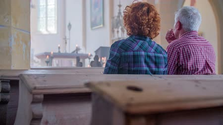 clergy : Two older Christians sitting down in pew and crossing themselves. The altar and frescos in the background. Close-up shot Stock Footage