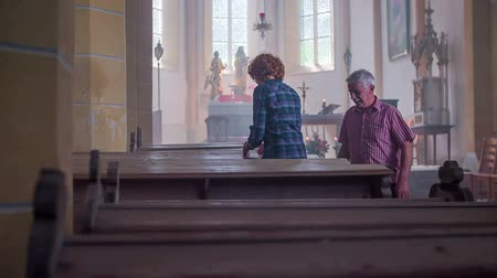 clergy : Old couple walking in the church on stone floor with altar at the back and sitting down in pew Stock Footage