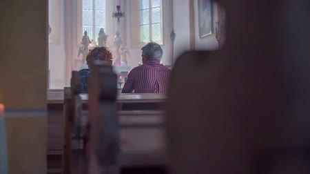 clergy : Senior couple seating on the bench in the church and praying beautiful scenery in the catholic church.