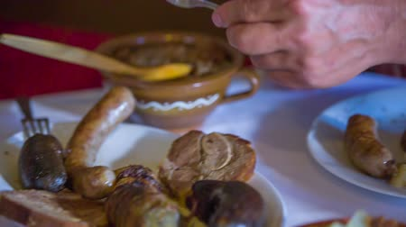cracknel : A man is putting a piece of sausage on his plate and cutting it in half. Close-up shot. There are also other types of food on a table. Stock Footage