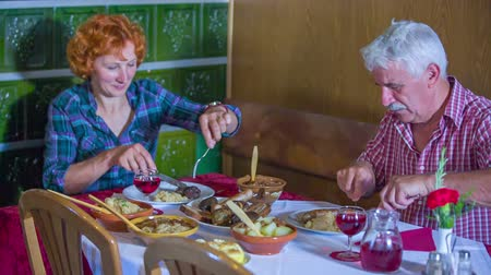 cracknel : An older couple is really enjoying their meal together in a restaurant that serves traditional food. The woman is cutting a bit of the sausage and putting it on her plate. Close-up shot.