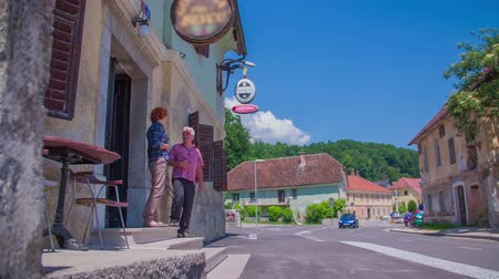 cracknel : A senior couple is walking out of the restaurant and into the street. The day looks very sunny and bright. They decide to walk towards the old town. Wide-angle shot. Stock Footage