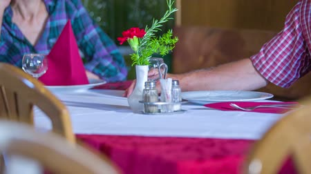 cracknel : A senior couple is waiting at a table in a restaurant and talking. The woman also unfolds her napkin. Close-up shot. We can only see the table cloth, the cutlery and their hands. Stock Footage