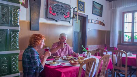cracknel : An older couple is toasting with red wine in an old-fashioned restaurant that serves local food. They are both enjoying their meal. Wide-angle shot. Stock Footage
