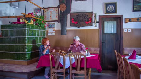 cracknel : An older couple is toasting with red wine in an old-fashioned restaurant. They are both having a great time. The restaurant is decorated in a very traditional way. There is an old farmhouse stove seen in the background and some photos too. Wide-angle shot